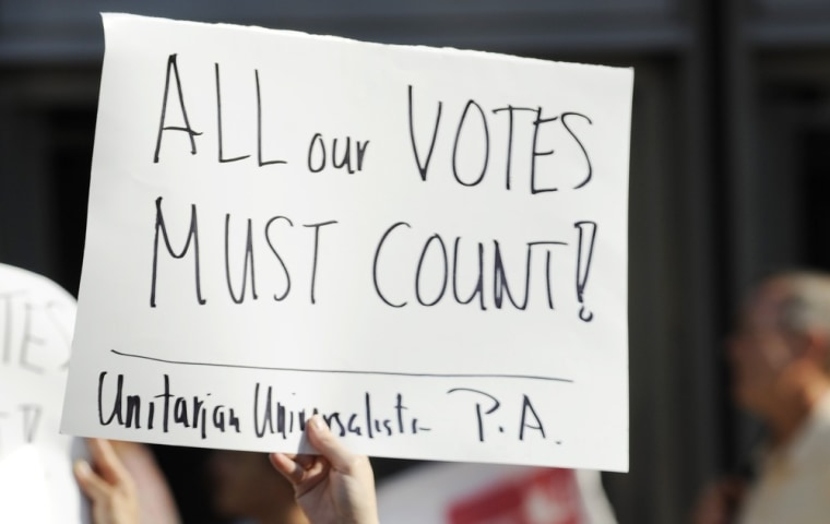 Emily Goldberg and her daughter Willa, 2, holds up a sign during the NAACP voter ID rally to demonstrate the opposition of Pennsylvania's new voter identification law, Thursday, September 13, 2012, in Philadelphia.
