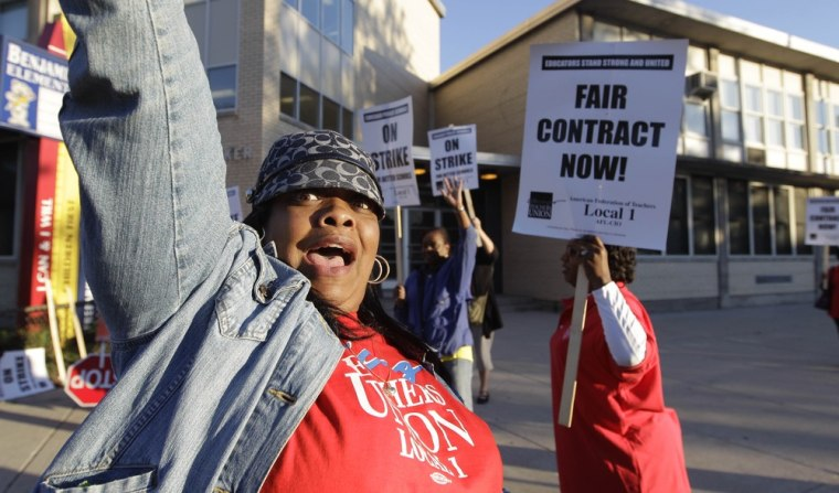 Chicago teachers walk a picket line outside Benjamin Banneker Elementary School in Chicago, Monday, Sept. 10, 2012, after they went on strike for the first time in 25 years.