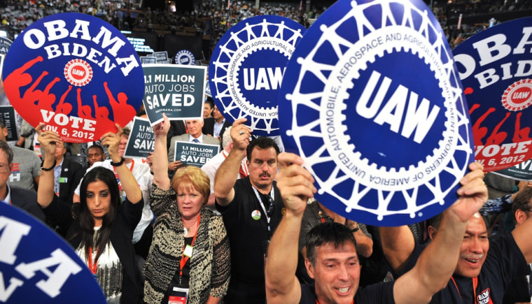 Supporters wave signs during President of the International Union, United Automobile, Aerospace and Agricultural Implement Workers of America (UAW)  Bob King 's address at the Time Warner Cable Arena in Charlotte, North Carolina, on September 5, 2012...