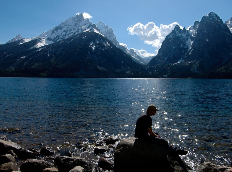 A hiker takes a break on the shore of Jenny Lake in Grand Teton National Park Tuesday, June 1, 2004.