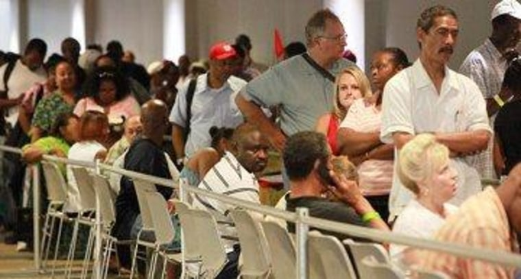 People wait in line to attend a free health care clinic for the uninsured.