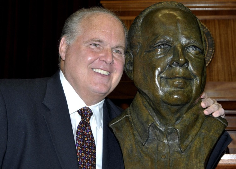 Conservative commentator Rush Limbaugh poses next to his gold bust. Limbaugh was inducted into the Hall of Famous Missourians on Monday, May 14, 2012.