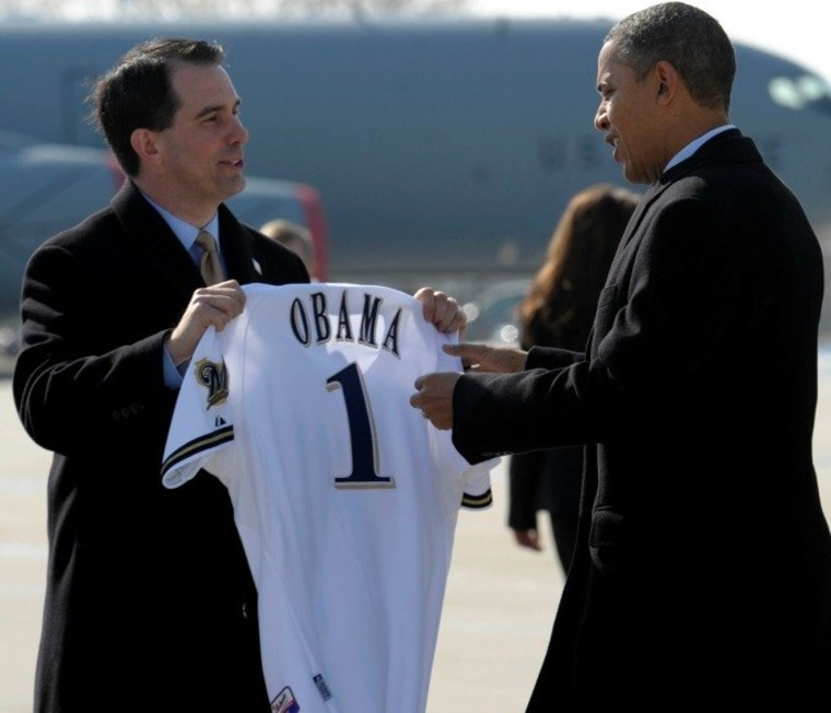Wisconsin Gov. Scott Walker presents President Barack Obama with a Milwaukee Brewers baseball jersey upon his arrival at General Mitchell International Airport in Milwaukee, Wednesday, Feb. 15, 2012.