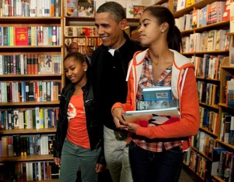 President Barack Obama visits Kramerbooks for shopping with his daughters Sasha, and Malia, right, Saturday, Nov. 26, 2011, in Washington.