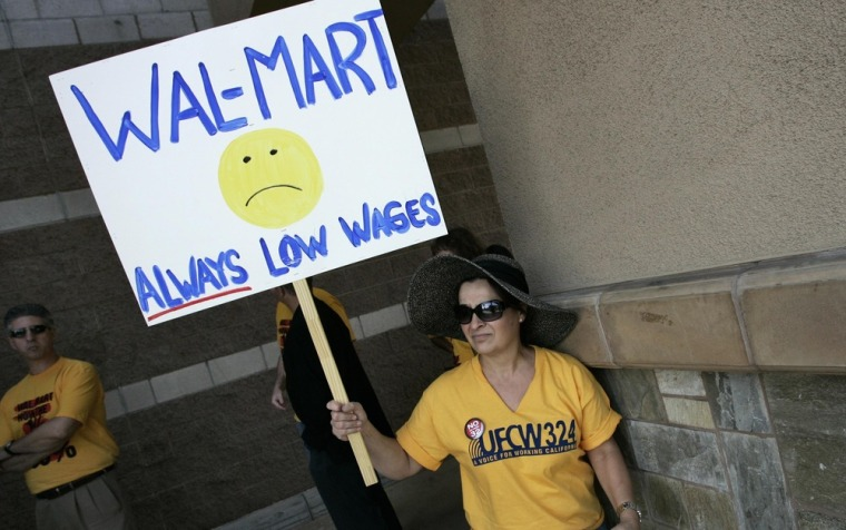 Diana Huffman holds a sign in support of striking Walmart workers protesting unsafe working conditions and poor wages outside a Walmart store in Pico Rivera, California, October 4, 2012.