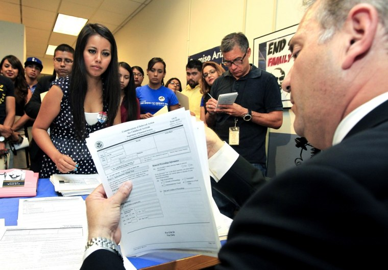 Gaby Perez, left, hands over all her paperwork to get guidance from immigration attorney Jose Penalosa, right, for a new federal program, called Deferred Action, that would help her avoid deportation, August 15. Schools and consulates have been flooded...