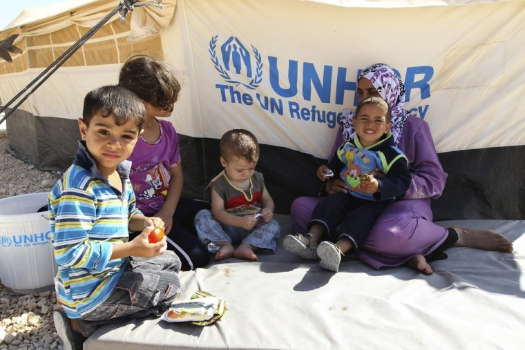 A Syrian refugee woman sits with her children during a visit by U.N. High Commissioner for Refugees (UNHCR) Antonio Guterres and Jordan's Foreign Minister Nasser Judeh to the Al Zaatri refugee camp in the Jordanian city of Mafraq September 11, 2012.