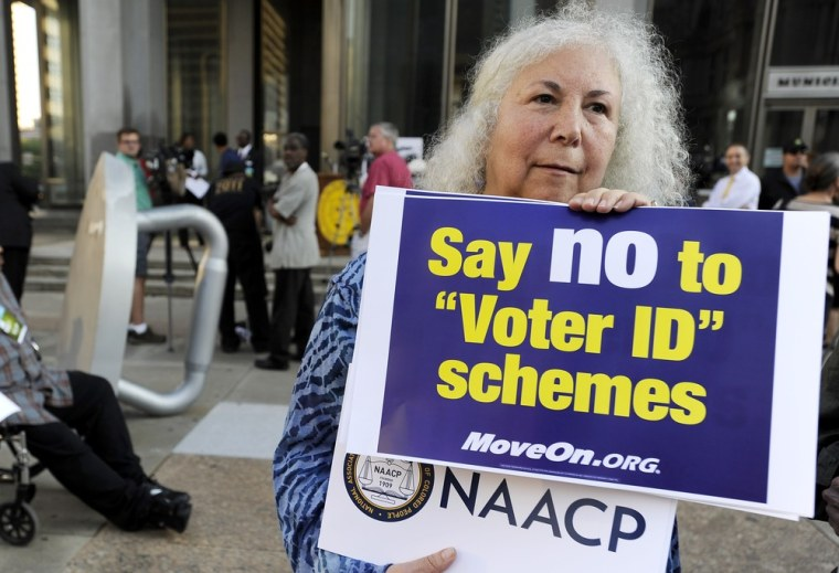 Gloria Gilman holds a sign during the NAACP voter ID rally to demonstrate the opposition of Pennsylvania's new voter identification law, Thursday, Sept. 13, 2012, in Philadelphia.