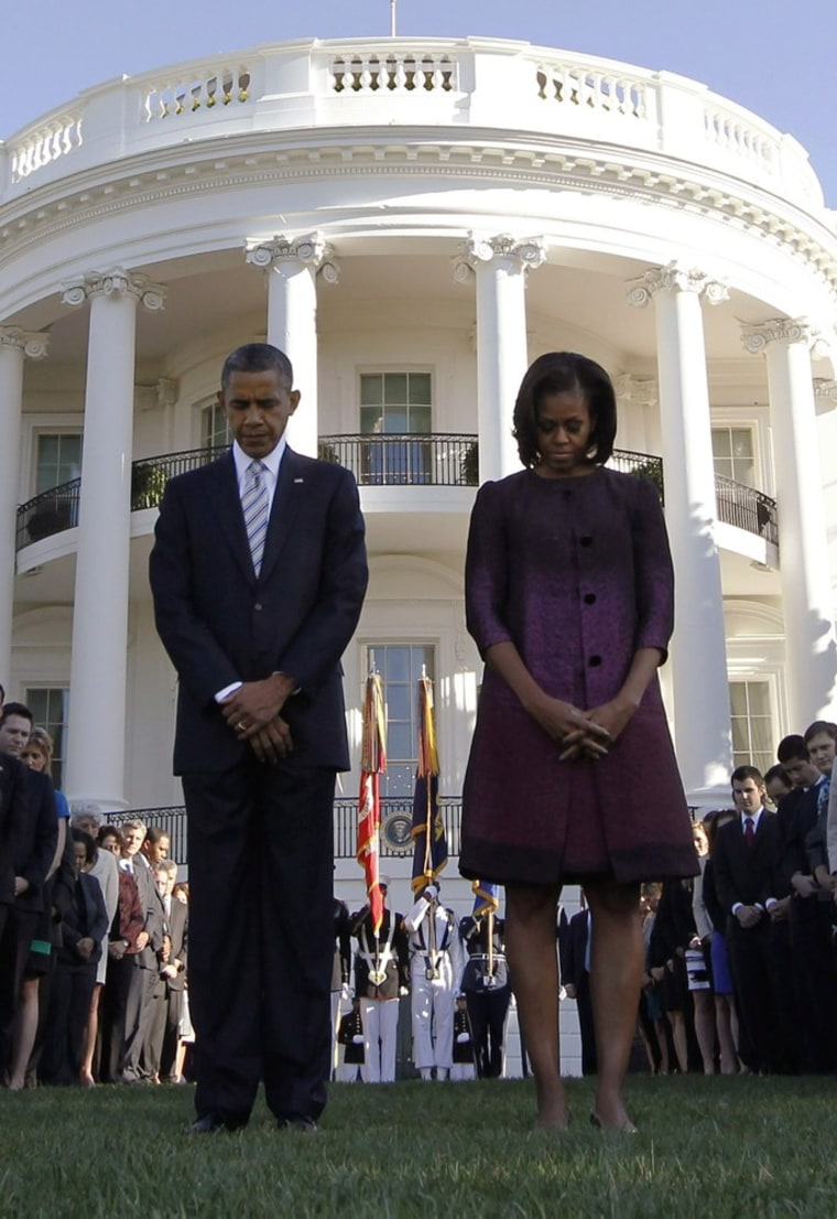 U.S. President Barack Obama and first lady Michelle Obama observe a moment of silence on the 11th anniversary of the September 11 attacks, on the South Lawn of the White House in Washington, September 11, 2012.