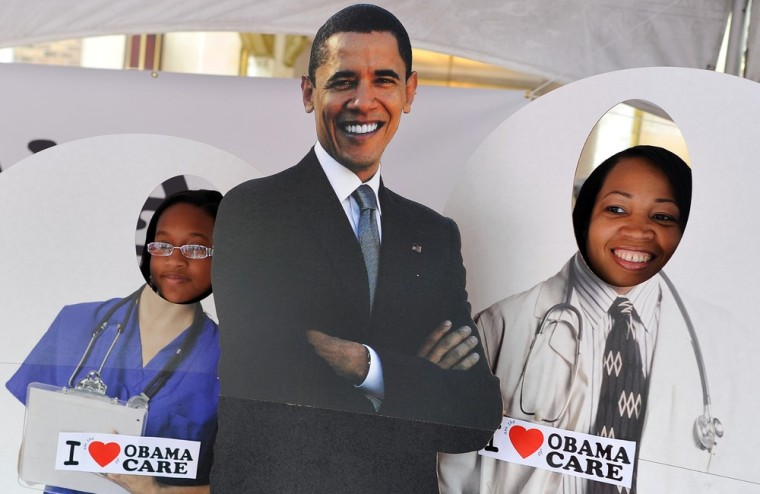 """Two girls pose for a picture with a cardboard cut-out of  US President Barack Obama in a tent defending \""""Obamacare\"""" at a street fair in Charlotte, North Carolina, September 3, 2012."""