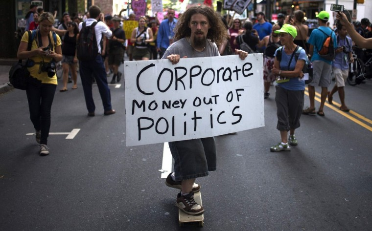 A demonstrator holds a placard while leading a protest from upon a skateboard through uptown Charlotte, the site of the Democratic National Convention in North Carolina on September 5, 2012.