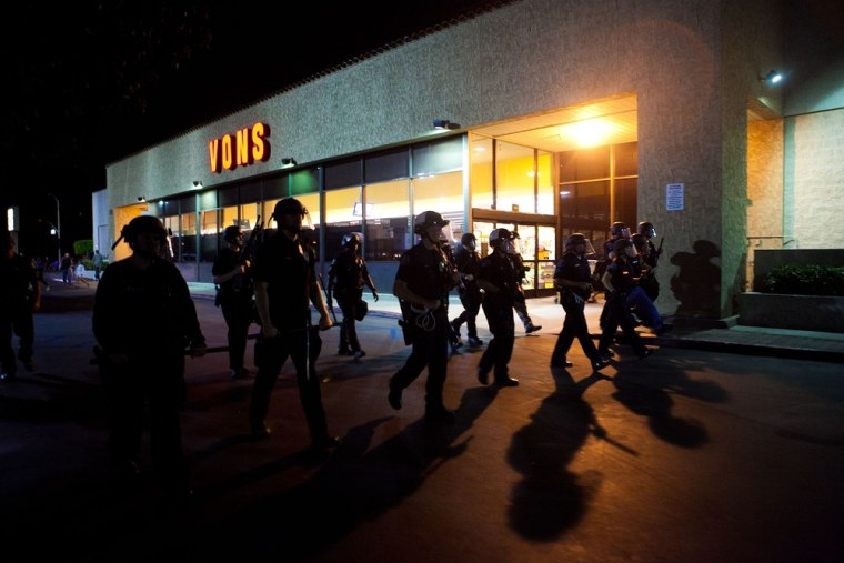 ANAHEIM, CA - JULY 24: A scrimmage line of police officers march through a shopping center after violence erupted between officers and protesters during demonstrations to show outrage for the fatal shooting of Manuel Angel Diaz, 25, at Anaheim City...