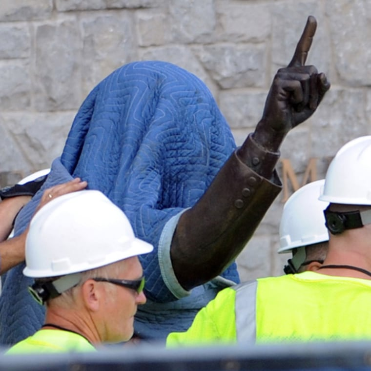 July 22, 2012 - State College, Pa. - Penn State workers cover the statue of former coach Joe Paterno near Beaver Stadium on Penn State's campus Sunday as they prepare to remove it.