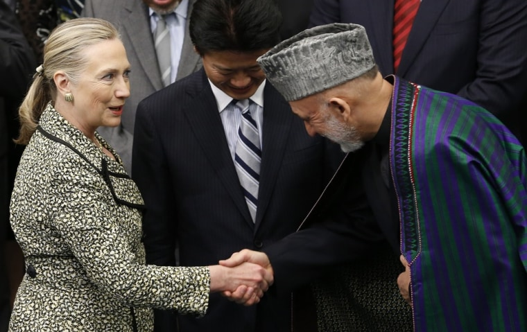U.S. Secretary of State Hillary Clinton shakes hands with Afghan President Hamid Karzai next to Japanese Foreign Minister Koichiro Gemba (C) during a photo session at the Tokyo Conference on the Reconstruction of Afghanistan, in Tokyo July 8.