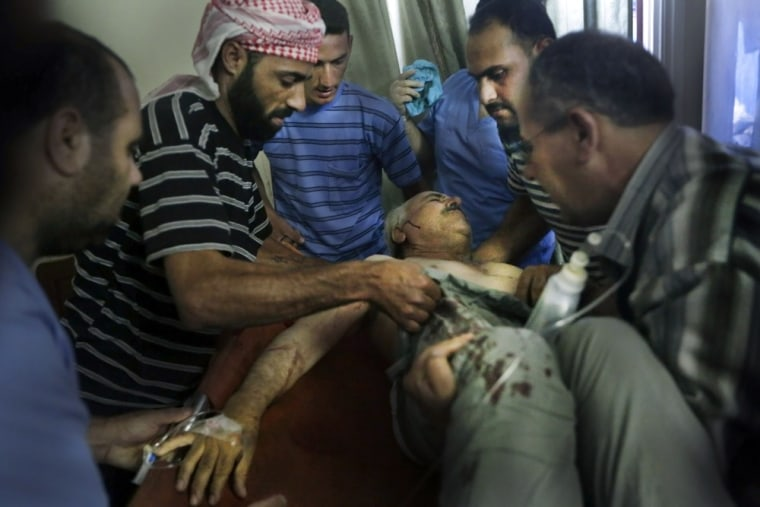A wounded man is lifted after shelling by Syrian government forces in Qusayr, close to the restive city of Homs, on Tuesday.