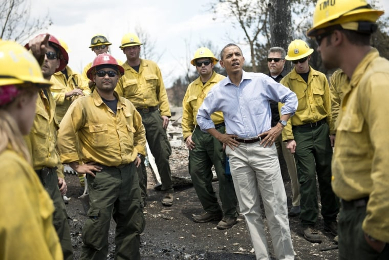 US President Barack Obama pauses with fire fighters while touring the Mountain Shadow neighborhood which was burned by wildfires about 72 hours ago, on June 29, 2012 in Colorado Springs, Colorado. Obama, who declared a major disaster in Colorado and...