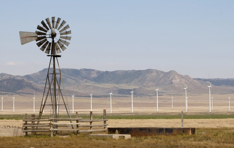 An old style windmill is pictured with newer and larger wind turbines in the background, at a wind farm near Milford, Utah May 21, 2012.