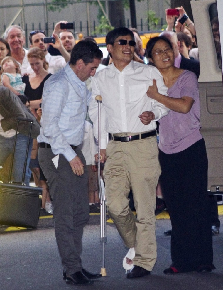Blind Chinese dissident Chen Guangcheng, center, is helped by his wife, Yuan Weijing, right, after arriving in New York on Saturday.