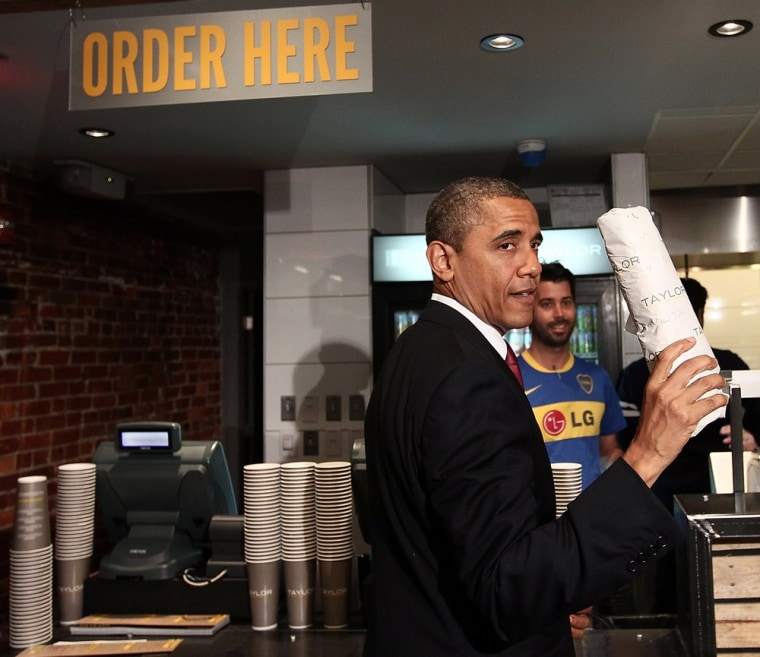 """WASHINGTON, DC - MAY 16:  U.S. President Barack Obama holds up a hoagie he purchased after visiting Taylor Gourmet, a sandwich restaurant, May 16, 2012 in Washington, DC. Obama is urging Congress to act on his """"To Do List,"""" specifically highlighting..."""