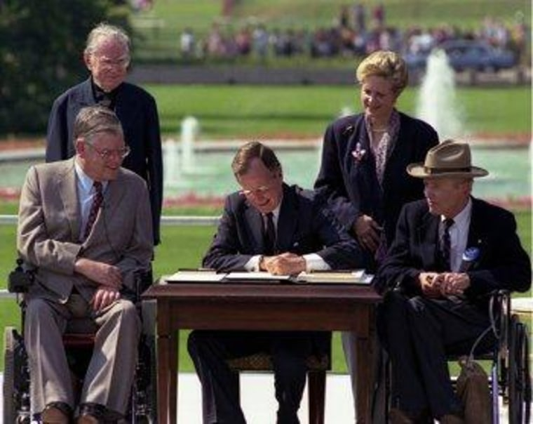 George H.W. Bush signs the Americans with Disabilities Act into law in 1990.