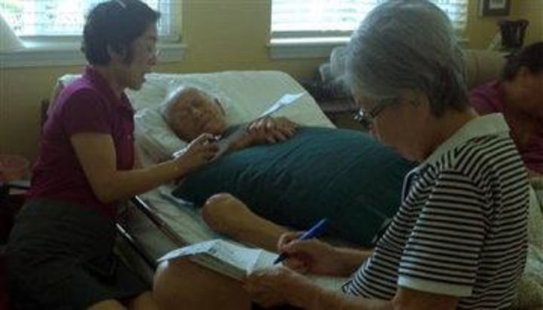 In this Oct. 17, 2012 photo provided by Irene Tanabe, 93-year-old World War II veteran Frank Tanabe, center, gets help from his daughter Barbara Tanabe, left, to fill out his absentee ballot in Honolulu while his wife Setsuko Tanabe sits in the...