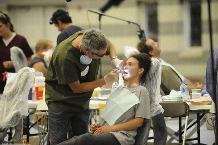 A dentist extracts a tooth from an uninsured patient at a mobile clinic in Sewanee, Tenn.