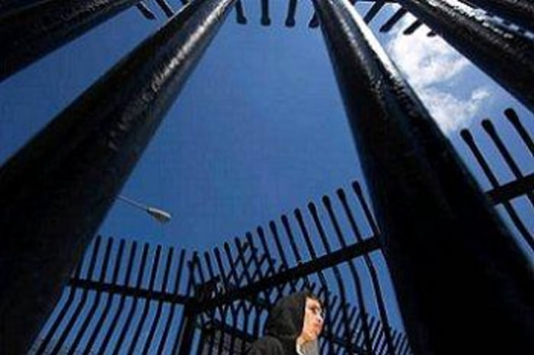 A youth stands in the gates at the U.S.-Mexico border awaiting his deportation at the port of entry in Tijuana.