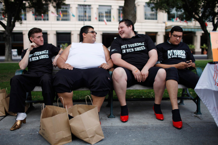 Bill Kincaid (L-R), Antonio Ayala, Robert Barrientos, and Chuy Jimenez share a bench while wearing women's high heels during the 10th annual Walk A Mile In Her Shoes to raise awareness against sexual violence in Plaza De Cesar Chavez in San Jose,...