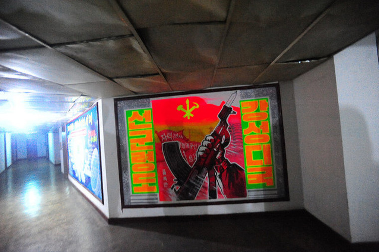 """The Yanggakdo Hotel in Pyongyang contains a mysterious, hidden fifth floor, a kind of bunker or meeting place. Calvin and his cohort found colorful propaganda posters, including this one. Calvin writes: 'Translation on the left side: """"military first..."""