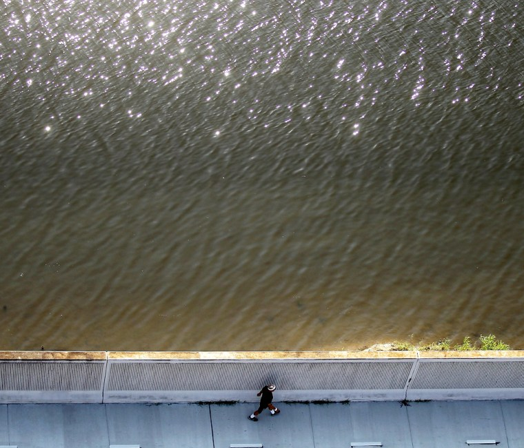 NEW ORLEANS - A man walks next to the 17th Street canal levee, which breached in the aftermath of Hurricane Katrina.