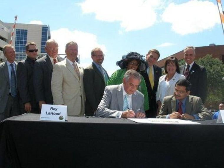 Transportation Secretary Ray LaHood signs a deal for $178.6 million in SunRail funding. Congressman Mica is at right in the yellow tie.