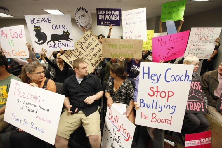 Protesters hold signs as they wait for the Virginia Board of Health meeting on abortion clinic regulations in Richmond, Va.