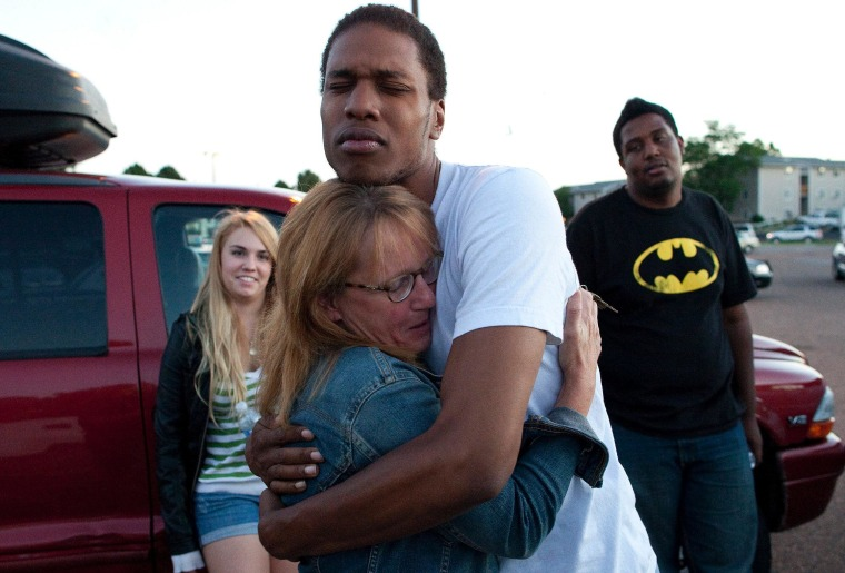 Judy Goos hugs her daughter's friend, Isaiah Bow, 20, while eye witnesses Emma Goos, 19, left, and Terrell Wallin, 20, right, gather outside Gateway High School where witnesses were brought for questioning early Friday morning in Denver.