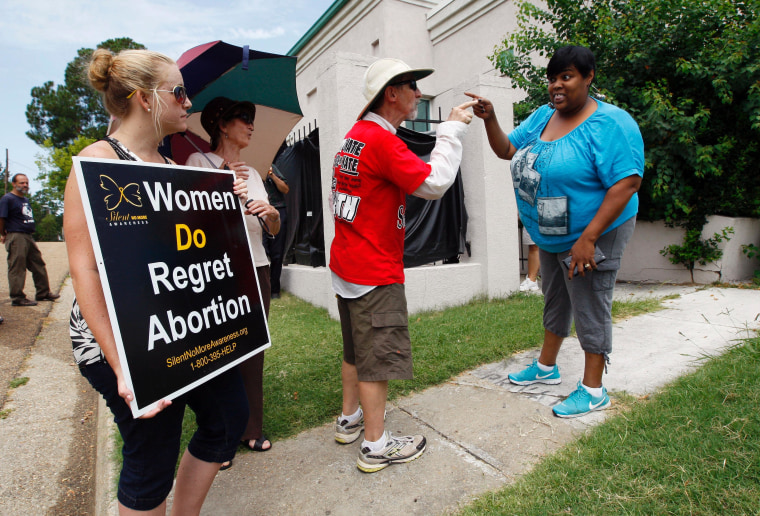Anti-abortion demonstrators argue with an administrator from Mississippi's only abortion clinic today after the state's anti-abortion law was blocked by a federal judge late yesterday.