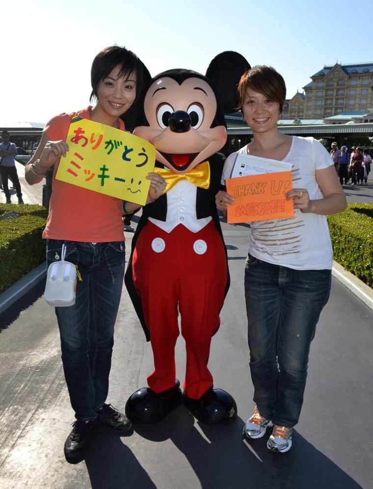 "Koyuki Higashi (L) and her partner Hiroko (R) display ""Thank you"" messages to Mickey Mouse at the Tokyo Disneyland in Urayasu, suburban Tokyo."