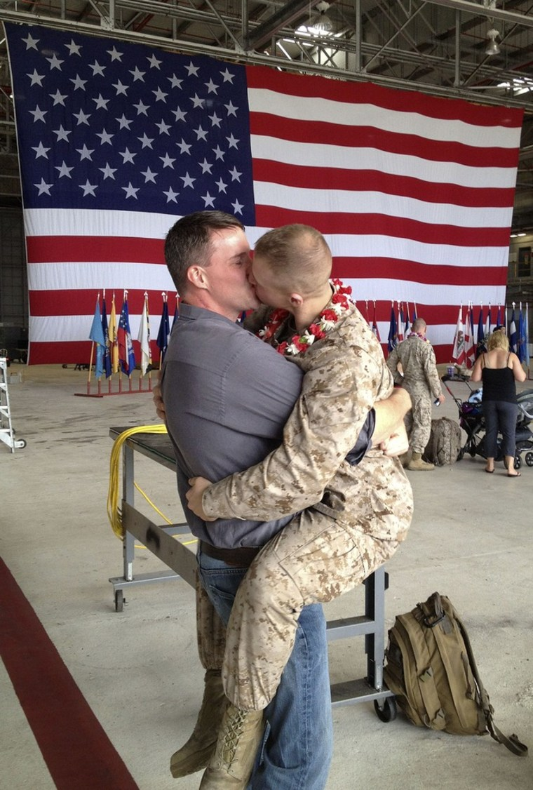 Sgt. Brandon Morgan, right, is embraced by his partner Dalan Wells in a helicopter hangar at a Marine base in Kaneohe Bay, Hawaii, upon returning from a six-month deployment to Afghanistan on February 22 of this year.