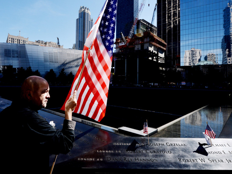 NEW YORK - SEPTEMBER 11:  Marshall Rodriguez of New York holds an American flag at the edge of the South Pool while visiting the names of friends he lost during memorial ceremonies for the eleventh anniversary of the terrorist attacks on lower...