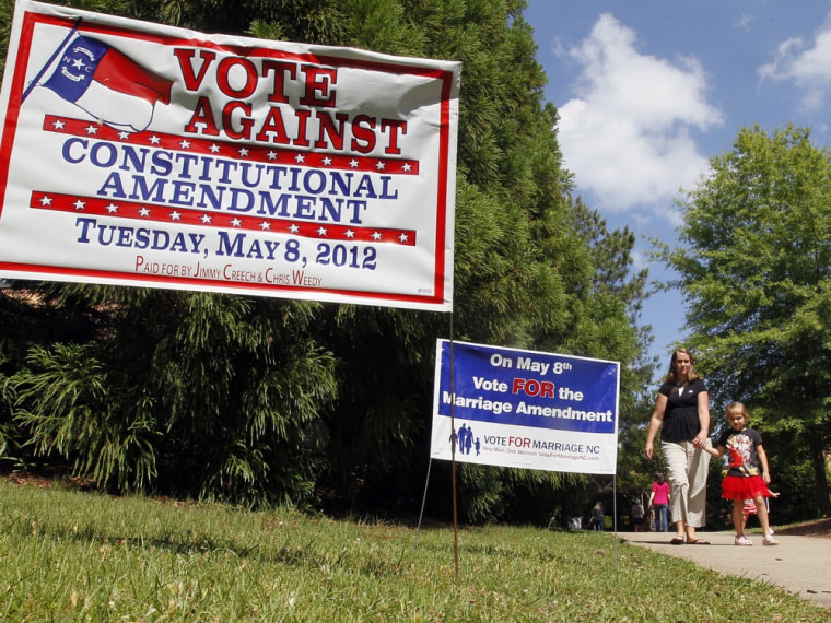 Signs in support of and against the Constitutional Marriage Amendment greet voters at a polling location at Leesville Road Middle School in Raleigh, N.C., Tuesday, May 8, 2012.