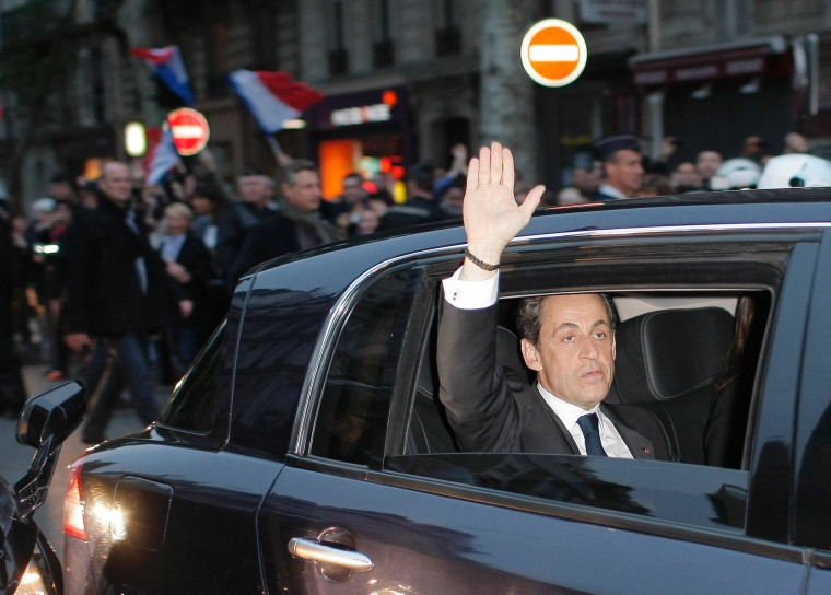 Outgoing French President Nicolas Sarkozy waves from his car as he leaves after addressing supporters at his Union for a Popular Movement (UMP) party headquarters after the the preliminary results of the second round of the presidential elections were...