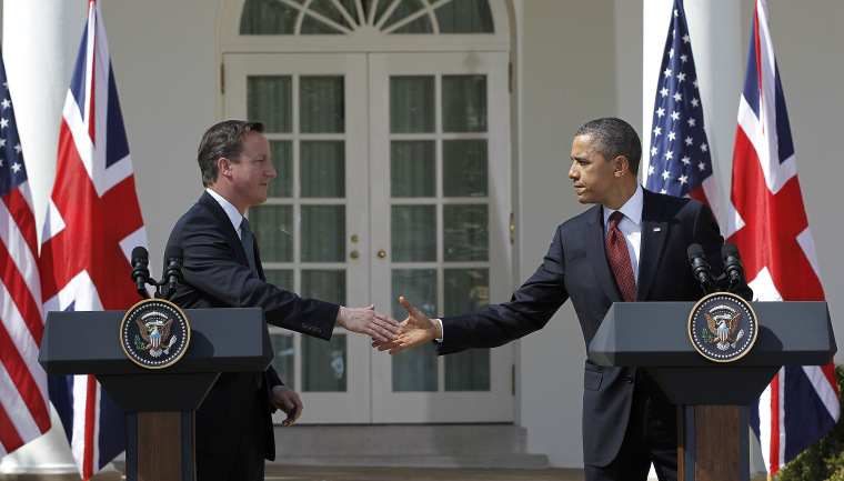 British Prime Minister David Cameron and President Barack Obama reach to shake hands during their joint news conference in the Rose Garden of the White House in Washington Wednesday, March 14, 2012