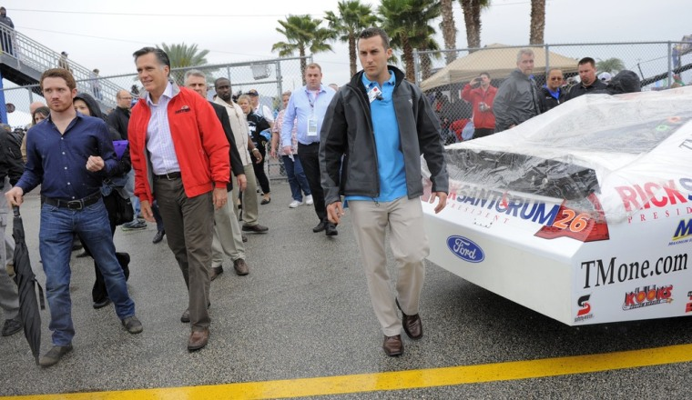Mitt Romney walks past the number 26 Ford, driven by Tony Raines, with advertising for Rick Santorum, at the Daytona 500 Sunday.
