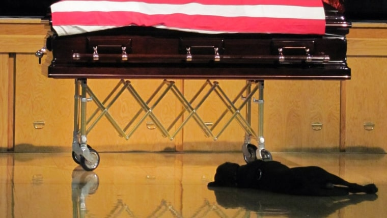 ROCKFORD, IA - AUGUST 19:  Labrador retriever Hawkeye lays by the casket during the funeral of his owner, Navy SEAL Jon Tumilson, 35, at the Rudd-Rockford-Marble Rock Community School August 19, 2011 in Rockford, Iowa. Tumilson was one of 38 killed on...