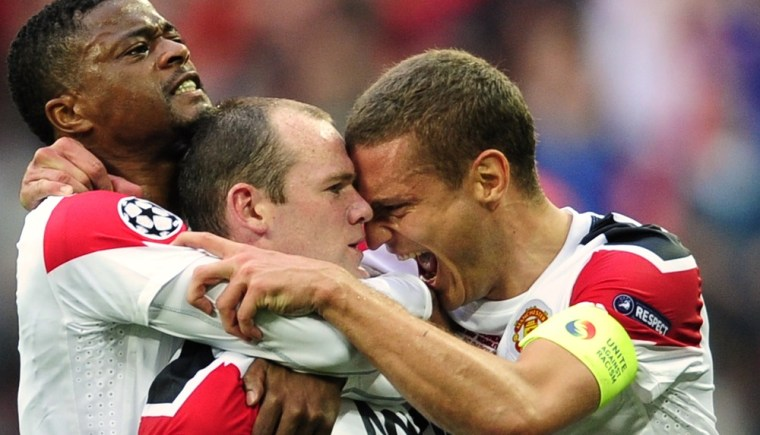 Manchester United's Wayne Rooney, center, celebrates scoring against Barcelona with teammates Patrice Evra, left, and Nemanja Vidic during their Champions League final soccer match at Wembley Stadium, London, Saturday, May 28, 2011.