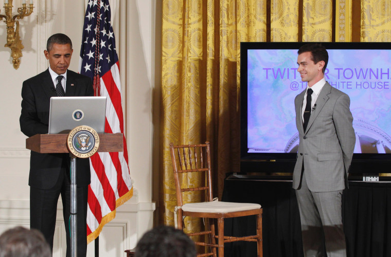 """President Barack Obama sends a tweet as Twitter co-founder and Executive Chairman Jack Dorsey stands at right, during a """"Twitter Town Hall"""" in the East Room of the White House in Washington, Wednesday, July 6, 2011."""