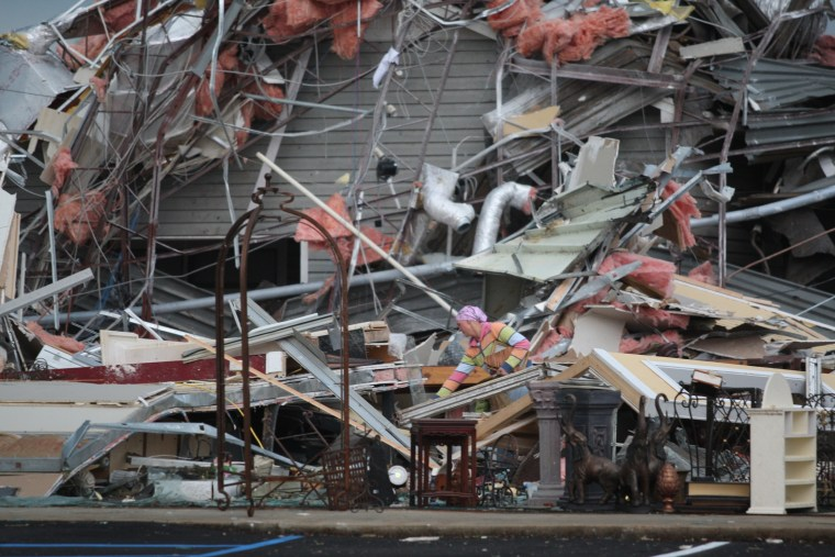 A woman sifts through the destruction of a former T Mobile office after a tornado struck, Wednesday, April 27, 2011 Tuscaloosa, Ala. wave of severe storms laced with tornadoes strafed the South on Wednesday, killing at least 16 people around the region...