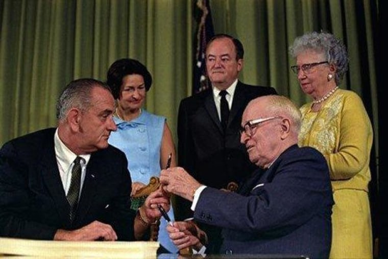 LBJ prepares to sign Medicare into law. Former President Harry Truman hands him the pen, as VP Hubert Humphrey, Lady Bird Johnson and Bess Truman look on.