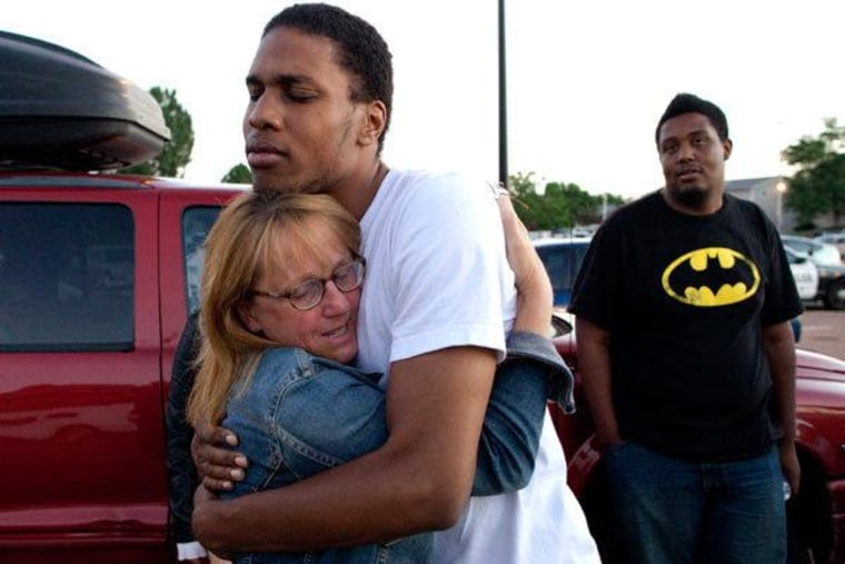 Judy Goos hugging her daughter's friend, Isaiah Bow, as Terrell Wallin looks on outside Gateway High School - the spot where witnesses were brought for questioning after the shooting.