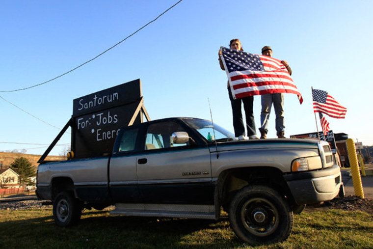 "Rick Santorum supporters hold the U.S. flag as they stand on a truck outside the site of the candidate's ""Super Tuesday"" primary party in Steubenville, Ohio."