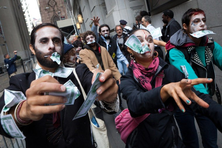 """Protesters from Occupy Wall Street marching through New York's financial district dressed as \""""corporate zombies\"""" on Monday."""