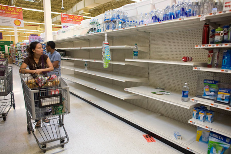 A shopper passes by empty shelves while looking for bottled water at a grocery store near Rockaway Beach in New York on Friday.